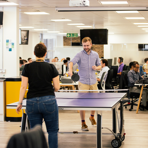 two employees playing ping pong