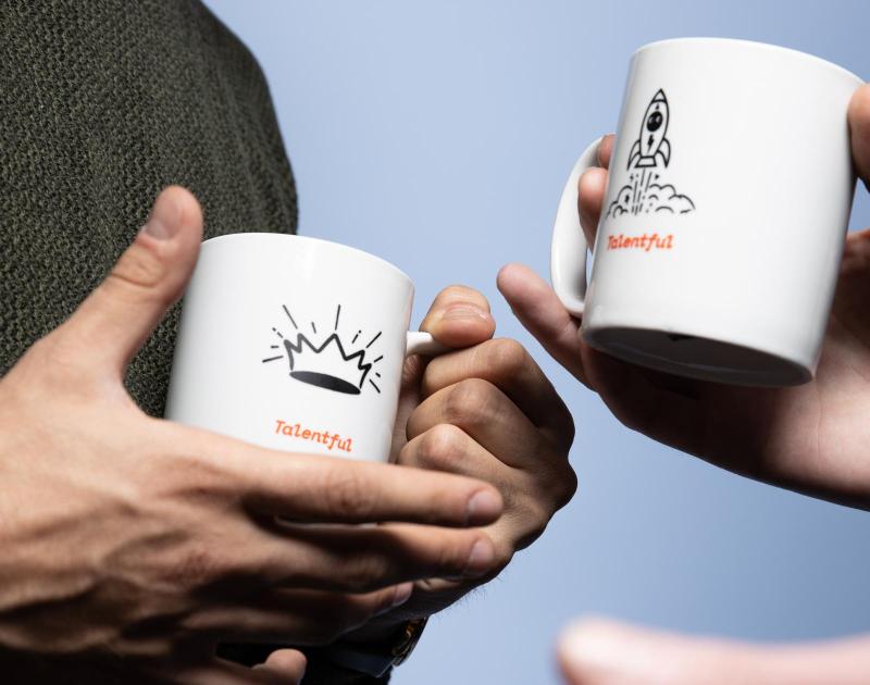two people holding talentful mugs