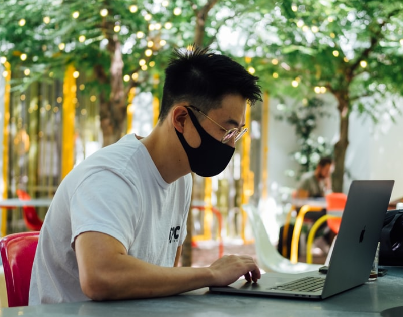man using laptop while wearing mask