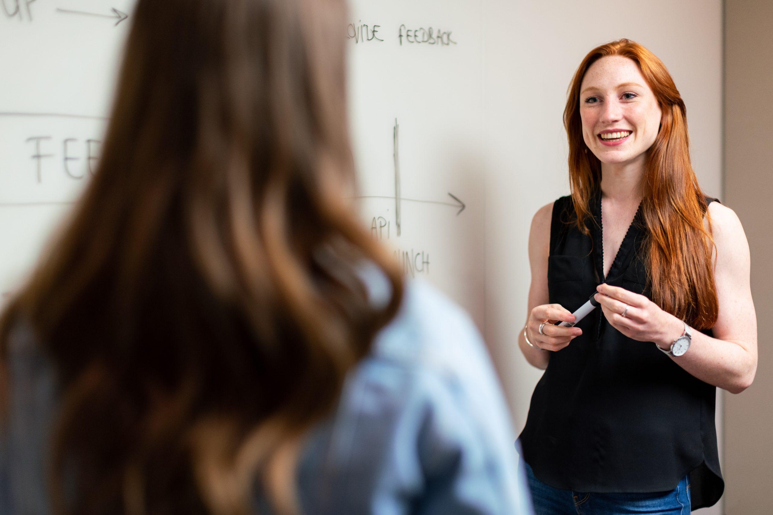 two women next to a whiteboard